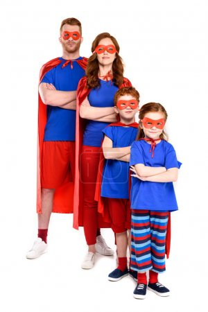 confident super family in costumes standing with crossed arms and looking at camera isolated on white