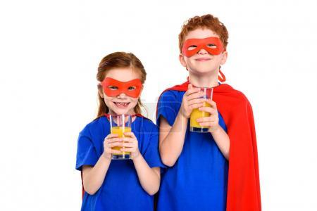 happy kids in superhero costumes holding glasses of juice and smiling at camera isolated on white