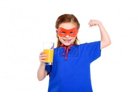happy child in superhero costume holding glass of juice and showing biceps isolated on white