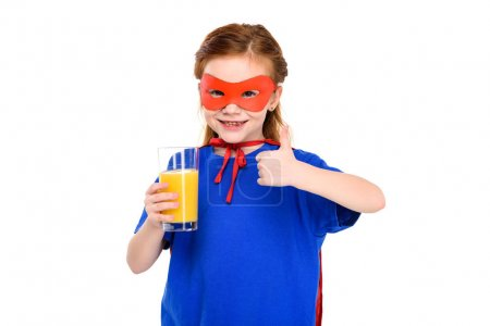child in superhero costume holding glass of juice and showing thumb up isolated on white
