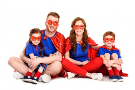 Photo for Happy super family in costumes sitting together and smiling at camera isolated on white - Royalty Free Image