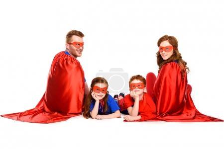 Foto de Familia feliz de superhéroes sentados juntos y sonriendo a cámara aislada en blanco - Imagen libre de derechos