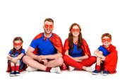 happy family of superheroes sitting together and smiling at camera isolated on white