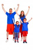 happy super family in costumes raising hands and smiling at camera isolated on white