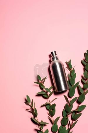 top view of metal bottle of perfume with green branches on pink surface