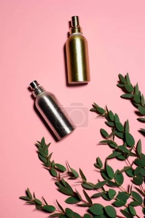 top view of metal bottles of perfumes with green branches on pink surface
