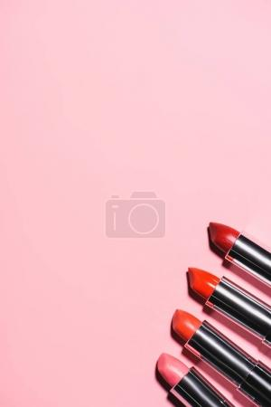 top view of different lipsticks in row on pink surface