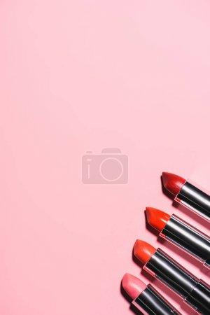Photo pour Vue du haut des différents rouges à lèvres en rangée sur la surface rose - image libre de droit
