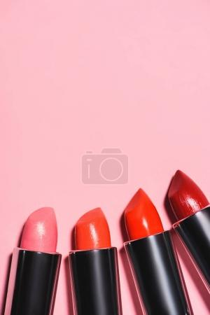 top view of different lipsticks on pink surface