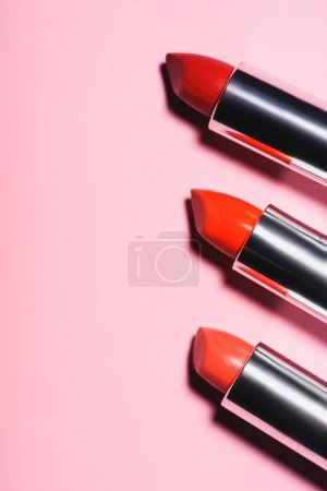 top view of various lipsticks of red shades in row on pink surface