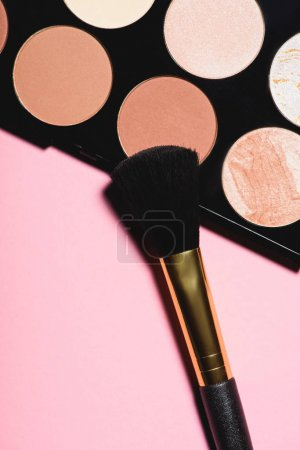 top view of different blushes palette with brush on pink surface