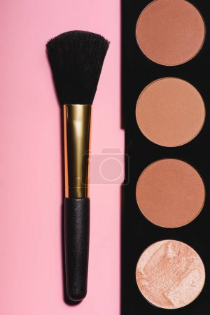 top view of bronzer palette with brush on pink surface