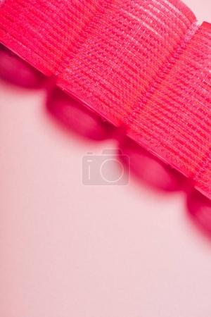 top view of red hair curlers in row on pink surface