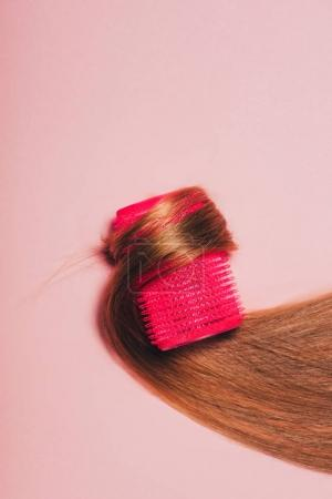 top view of hair rolled over curler on pink surface