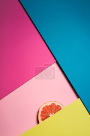 top view of slice of grapefruit on colorful surfaces