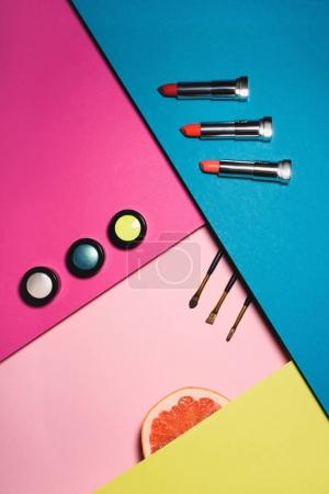 top view of various makeup supplies with grapefruit slice on colorful surfaces