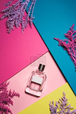 top view of bottle of perfume with purple branches on colorful surface