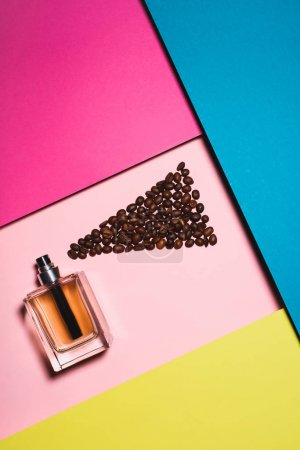 top view of glass bottle of perfume with coffee beans on colorful surface