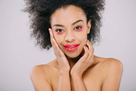 happy young african american woman with red lips and red paint strokes under eyes isolated on grey