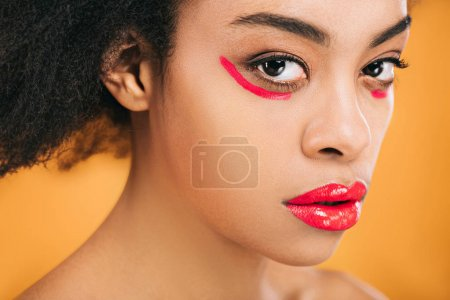 close-up portrait of young woman with creative red makeup isolated on yellow