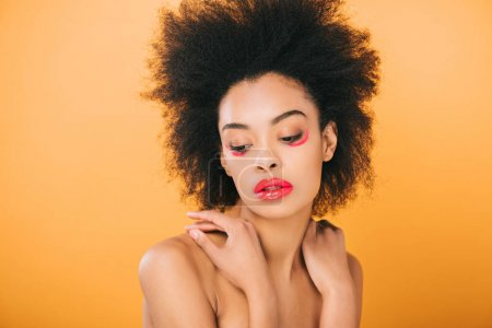 beautiful young woman with creative red makeup and afro hairstyle isolated on yellow