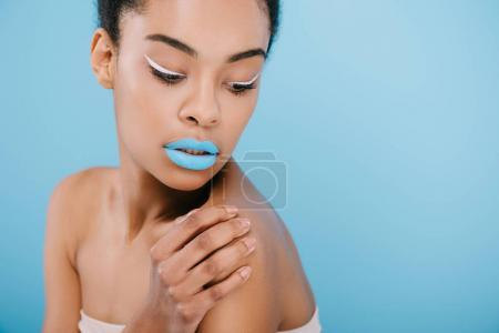 seductive african american woman with creative makeup and blue lips on blue