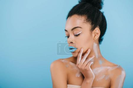 sensual young woman with creative makeup and blue lips isolated on blue