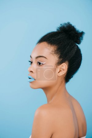 attractive young woman with creative makeup looking away isolated on blue