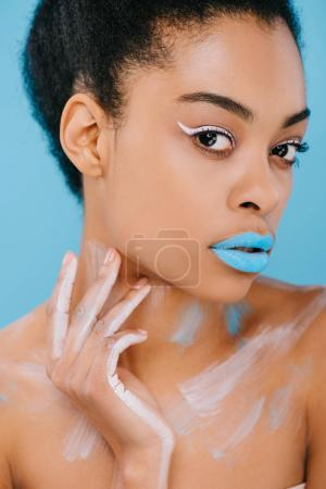young african american woman with creative makeup and perfect skin looking at camera isolated on blue