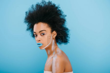 beautiful young woman with creative makeup and afro hairstyle isolated on blue
