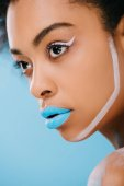 close-up portrait of young woman with creative makeup and blue lips isolated on blue