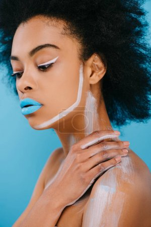 young afro woman with creative makeup and blue lips isolated on blue