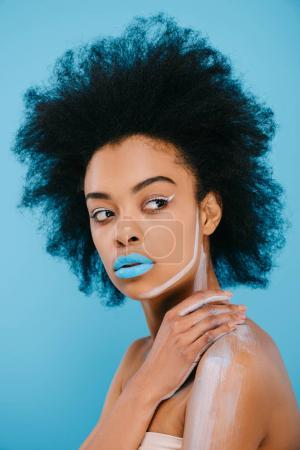 attractive young woman with creative makeup and blue lips isolated on blue