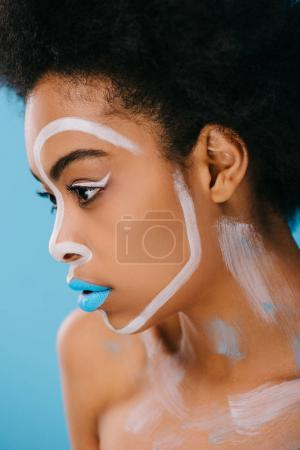 close-up portrait of beautiful young woman with creative makeup isolated on blue