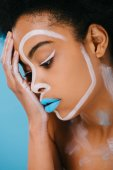 attractive young woman with creative makeup isolated on blue