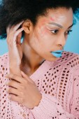 young african american woman with creative makeup in sweater isolated on blue