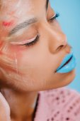 close-up portrait of young african american woman with creative makeup isolated on blue