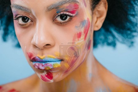 african american woman with paint strokes on face looking at camera isolated on blue
