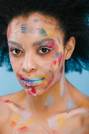 young african american woman with paint strokes on face looking at camera isolated on blue