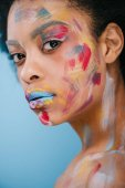 beautiful young woman with paint strokes on face isolated on blue