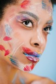 close-up portrait of attractive young woman with paint strokes on face isolated on blue