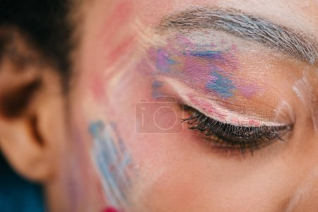 cropped shot of woman with colorful strokes on face with closed eye