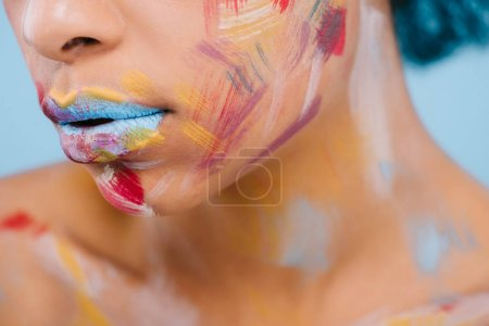 cropped shot of woman with colorful strokes on face on blue