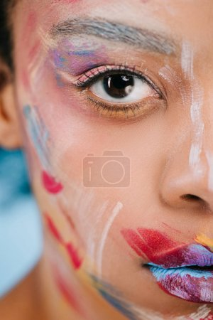 cropped shot of young woman with colorful strokes on face looking at camera on blue