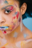 close-up portrait of beautiful young woman with colorful strokes on face on blue