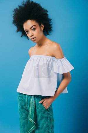 young african american woman in stylish off-the-shoulder top isolated on blue