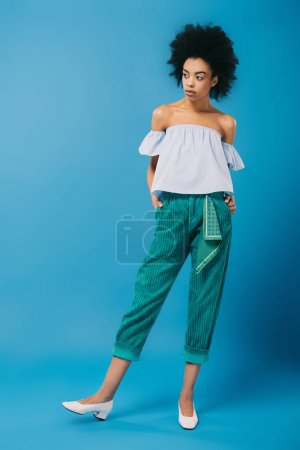 attractive young woman in stylish off-the-shoulder top on blue