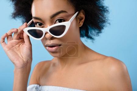 Photo pour Portrait en gros plan de belle jeune femme aux élégantes lunettes de soleil rétro isolées sur bleu - image libre de droit