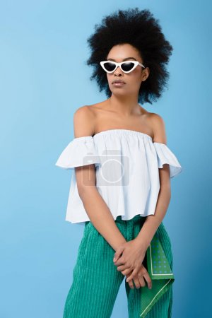 young african american woman in stylish off-the-shoulder top and sunglasses isolated on blue