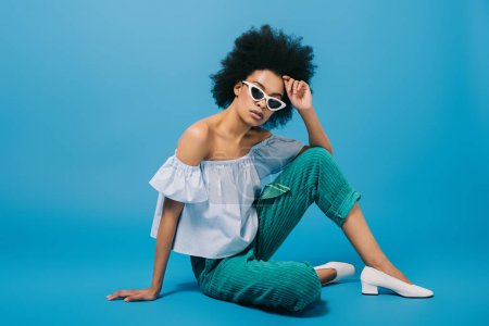 attractive young woman in stylish off-the-shoulder top and sunglasses sitting on floor on blue